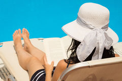 Woman reading a book by the swimming pool Stock Photos
