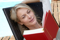 Woman reading book by swimming pool Stock Photography