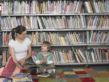 Woman Reading Book To Boy In Library Stock Photos