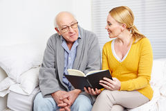Woman reading book to senior man. Woman reading a book to a senior citizen men in nursing home Stock Photography