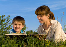 Woman, reading a book to the young boy Stock Photography