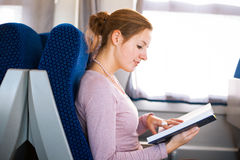 Woman reading a book while on a train Royalty Free Stock Photography