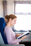Woman reading a book while on a train