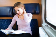 Woman reading a book while on a train Royalty Free Stock Image