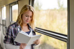 Woman reading a book by train window Stock Photos