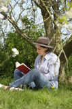 Woman reading a book under a tree Royalty Free Stock Images