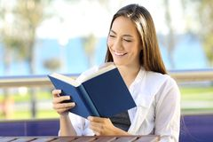 Woman reading a book during vacations on the beach. Happy woman reading a book during vacations sitting in an apartment balcony on the beach stock image