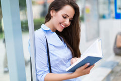 Woman reading book while waiting for bus Royalty Free Stock Photos