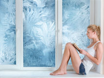 Woman reading book in warm room. Woman reading a book in warm room meanwhile cold winter behind her window Royalty Free Stock Photos