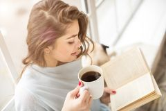 Book and drinks. Woman reading book white having a cup of fragrant coffee. Relaxed mood lovely hobby time. Woman reading book white having a cup of fragrant Stock Image
