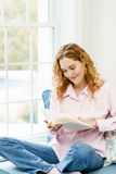 Woman reading book by window Stock Photos