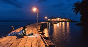Woman reading book on a wooden warf at night . Royalty Free Stock Photo