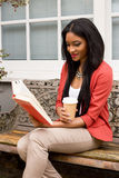 Woman reading a book. Young woman reading a book with a coffee Royalty Free Stock Image