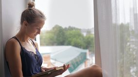 Woman reading a book. Young woman reading a book, sitting on the windowsill stock footage