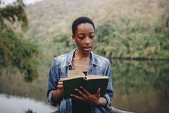Woman reading a booking in forest stock photos