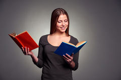 Woman reading the books. Smiley pretty woman reading the books over dark background Royalty Free Stock Photos