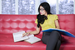 Woman reading books on couch with winter background Stock Photo