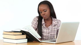 Woman reading books with a laptop stock video footage