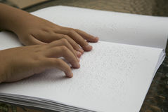 Woman reading Braille book. A girl reads a braille book by placing her fingers over the special characters in a library in the Spanish island of Mallorca Stock Photo