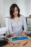 Woman reading business graphic charts next to her laptop Stock Photos
