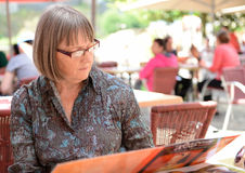 Woman reading cafe menu. Portrait of middle-aged woman reading a menu in a cafe or restaurant Royalty Free Stock Photography