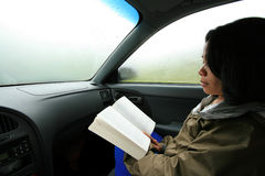 Woman Reading in Car During Rain Royalty Free Stock Photo