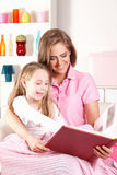 Woman reading for child Stock Images