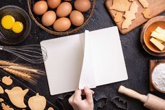 Woman is reading cookbook recipe of making Halloween cookies with baking ingredients, design concept of cooking class, top view,