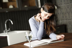 Woman reading a cookery book Stock Photography