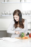 Woman reading cookery book Stock Images