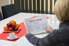 Woman reading crisis article. In the newspaper at home Royalty Free Stock Images
