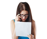 Woman reading document. Brunette young woman shocked realizes that something amazing or bad happened reading a white letter or document stock photos
