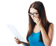 Woman reading document. Brunette young woman shocked realizes that something amazing or bad happened reading a white letter or document royalty free stock photography