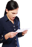 Woman reading document. Brunette young woman shocked realizes that something amazing or bad happened reading a white letter or document royalty free stock photo