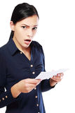 Woman reading document. Brunette young woman shocked realizes that something amazing or bad happened reading a white letter or document stock image
