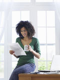 Woman reading document at home Stock Images