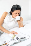 Woman reading and drinking coffee on bed Royalty Free Stock Photos
