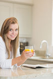 Woman reading while drinking orange juice Royalty Free Stock Photos