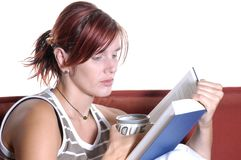 Woman reading and drinking tea Stock Image