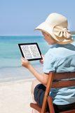 Woman Reading E-Book At Beach Stock Image