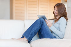 Woman reading e-book on the couch Royalty Free Stock Photography