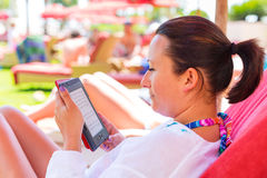 Woman reading on e-book on holidays Royalty Free Stock Images