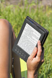 Woman reading e-book outdoor Royalty Free Stock Image