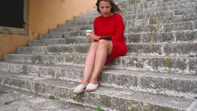 Woman reading an e-book sitting on the steps outdoors stock video footage
