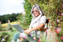 Woman reading ebook from garden Stock Photography
