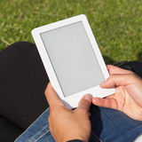Woman reading ebook on the grass Royalty Free Stock Photo