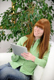 Woman reading an ebook on her digital tablet Royalty Free Stock Photography