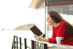 Woman reading an ebook on holidays. Side view of happy woman wearing a red sweater reading an ebook in an hotel or apartment on the beach on holidays Royalty Free Stock Image