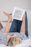 Woman Reading Ebook While Lying On Bed Royalty Free Stock Images