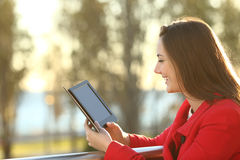 Woman reading ebook at sunset Royalty Free Stock Photos